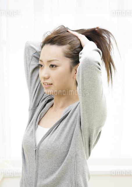 髪を束ねる若い女性の写真素材 [FYI03039013]