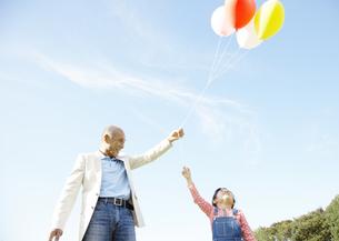 風船で遊ぶ祖父と孫の写真素材 [FYI03039175]