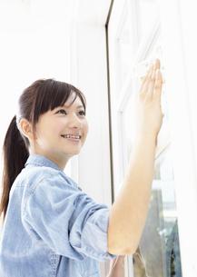 窓を拭く若い女性の写真素材 [FYI03040228]