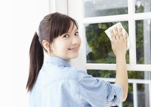窓を拭く若い女性の写真素材 [FYI03040230]