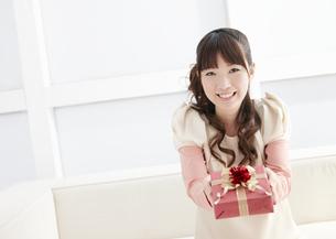 プレゼントを差し出す若い女性の写真素材 [FYI03040284]