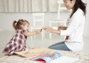 母親にお菓子を渡す女の子の写真素材 [FYI03040503]