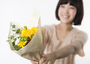 花束を差し出す女性の写真素材 [FYI03041266]