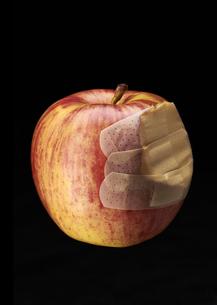 絆創膏が貼られた食べかけのリンゴの写真素材 [FYI03041410]