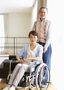 車椅子の妻のそばに立つシニア男性の写真素材 [FYI03041790]
