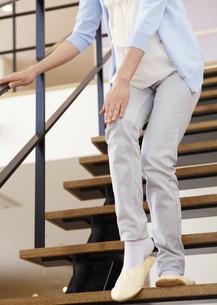 階段で膝を押さえるシニア女性の写真素材 [FYI03041796]