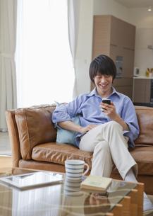 ソファに座ってスマートフォンを操作するミドル男性の写真素材 [FYI03041799]