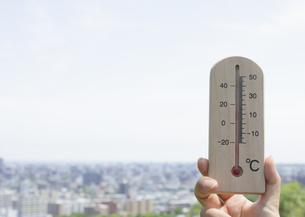 温度計を持つ手と町並の写真素材 [FYI03041860]