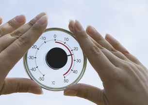 丸い温度計を持つ手の写真素材 [FYI03041862]