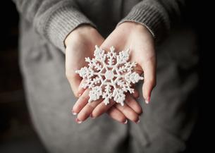 雪の結晶のオーナメントを持つ女性の写真素材 [FYI03042493]