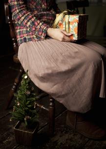 ギフトボックスを持つ女性とクリスマスツリーの写真素材 [FYI03042503]