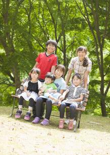 ベンチに座った大家族の兄弟姉妹の写真素材 [FYI03042638]