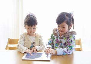 タブレットPCで遊ぶ姉妹の写真素材 [FYI03043847]