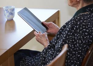 タブレットPCを触る90代女性の写真素材 [FYI03043857]