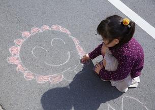 チョークでお絵描きする女の子の写真素材 [FYI03043909]