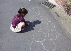 チョークでお絵描きする女の子の写真素材 [FYI03043916]