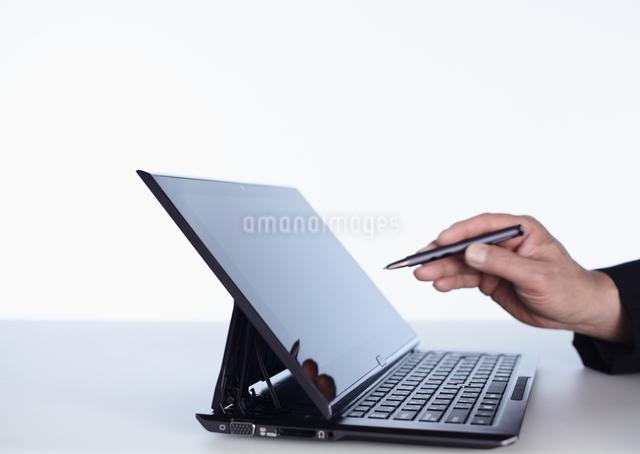 タブレットPCをタッチペンで操作する手の写真素材 [FYI03043958]