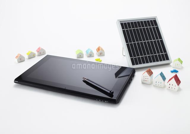 タブレットPCとソーラー充電器とミニチュアの家の写真素材 [FYI03043967]