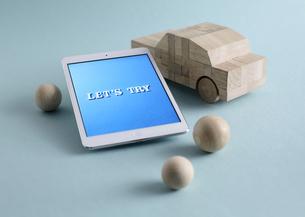 木製の車のおもちゃとタブレットPCの写真素材 [FYI03044003]