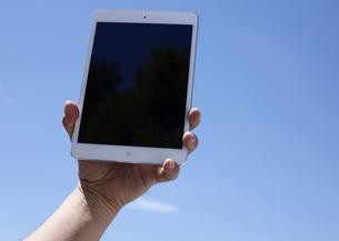 青空とタブレットPCを持つ手の写真素材 [FYI03044007]