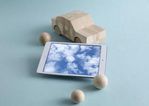 木製の車のおもちゃとタブレットPCの写真素材 [FYI03044008]