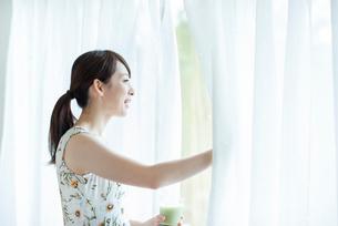 スムージーを持ちカーテンを開ける女性の写真素材 [FYI03044754]