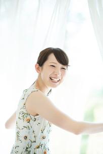 カーテンを開け微笑む女性の写真素材 [FYI03044756]