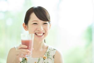 スムージーを持ち微笑む女性の写真素材 [FYI03044757]