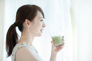 窓辺でスムージーを飲む女性の写真素材 [FYI03044763]