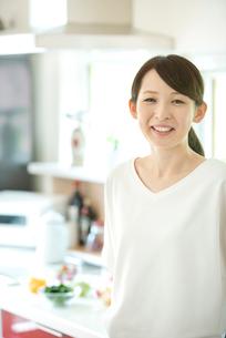 キッチンで微笑む女性の写真素材 [FYI03044768]
