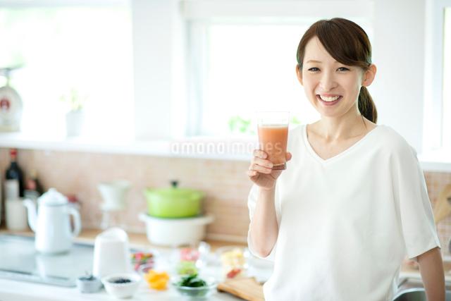 キッチンでスムージーを持ち微笑む女性の写真素材 [FYI03044769]