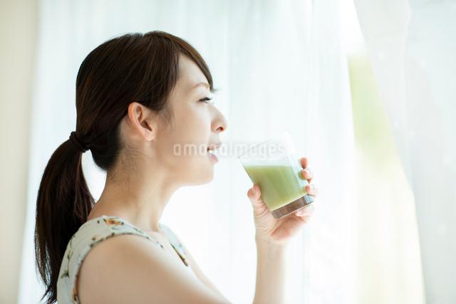 窓辺でスムージーを飲む女性の写真素材 [FYI03044770]