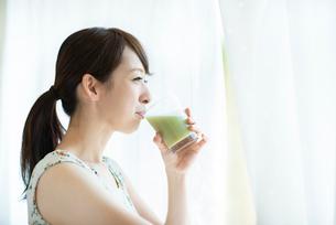 窓辺でスムージーを飲む女性の写真素材 [FYI03044775]