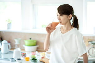 キッチンでスムージーを飲む女性の写真素材 [FYI03044782]