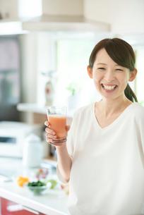 キッチンでスムージーを持ち微笑む女性の写真素材 [FYI03044787]