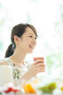 スムージーを持ち微笑む女性の写真素材 [FYI03044788]
