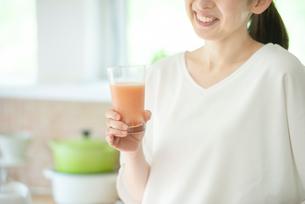 キッチンでスムージーを持つ女性の手元の写真素材 [FYI03044799]