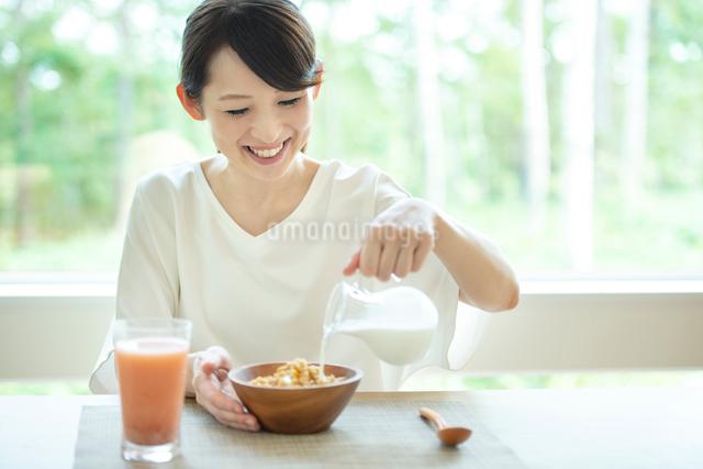 シリアルに牛乳を注ぐ女性の写真素材 [FYI03044802]