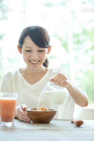 シリアルに牛乳を注ぐ女性の写真素材 [FYI03044803]