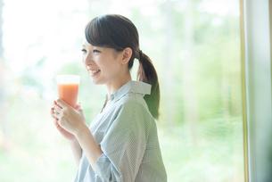 窓辺でスムージーを持ち微笑む女性の写真素材 [FYI03044814]