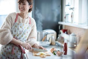 キッチンで振り向く女性の写真素材 [FYI03044991]
