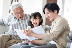 絵本を読む3世代家族の写真素材 [FYI03045028]