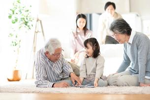 絵本を読む3世代家族の写真素材 [FYI03045029]