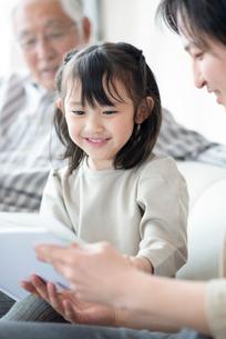 絵本を読む3世代家族の写真素材 [FYI03045030]