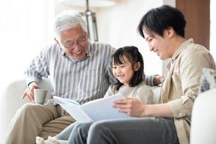絵本を読む3世代家族の写真素材 [FYI03045031]