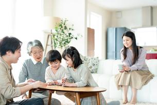 トランプで遊ぶ3世代家族の写真素材 [FYI03045036]