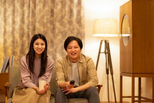 ソファーに座りテレビを見るカップルの写真素材 [FYI03045051]
