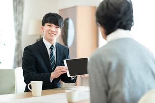 シニア女性に説明をするビジネスマンの写真素材 [FYI03045070]