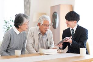 ビジネスマンと話をするシニア夫婦の写真素材 [FYI03045074]