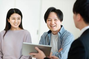 ビジネスマンと話をする夫婦の写真素材 [FYI03045078]